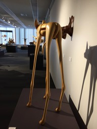 Rear view of a wooden sculpture of a very small dog on very tall skinny legs.