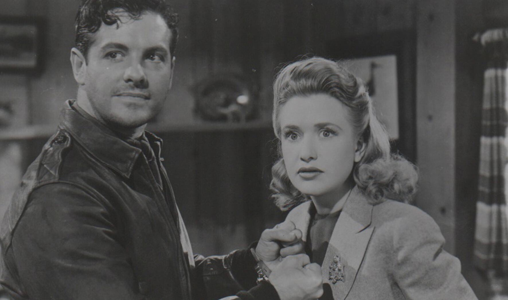 """Black and white photo of Robert Cummings (on left) and Priscilla Lane (on right) in Alfred Hitchcock's film """"Saboteur""""."""